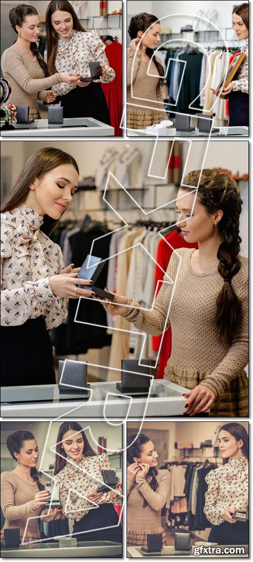Young woman choosing jewellery with shop assistant help - Stock photo