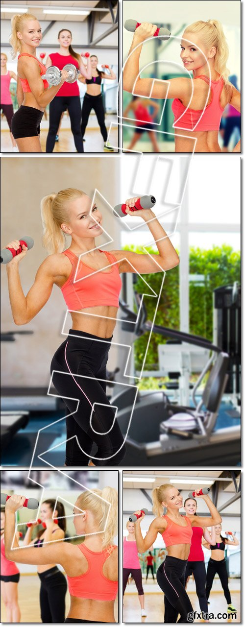 Smiling beautiful sporty woman with dumbbells - Stock photo