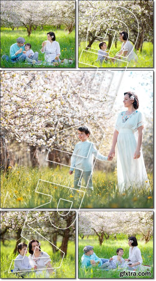 Young family picnicking in blooming apple garden - Stock photo