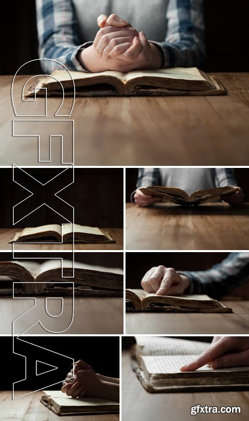 Stock Photos - Woman Reading The Bible In The Darkness Over Wooden Table