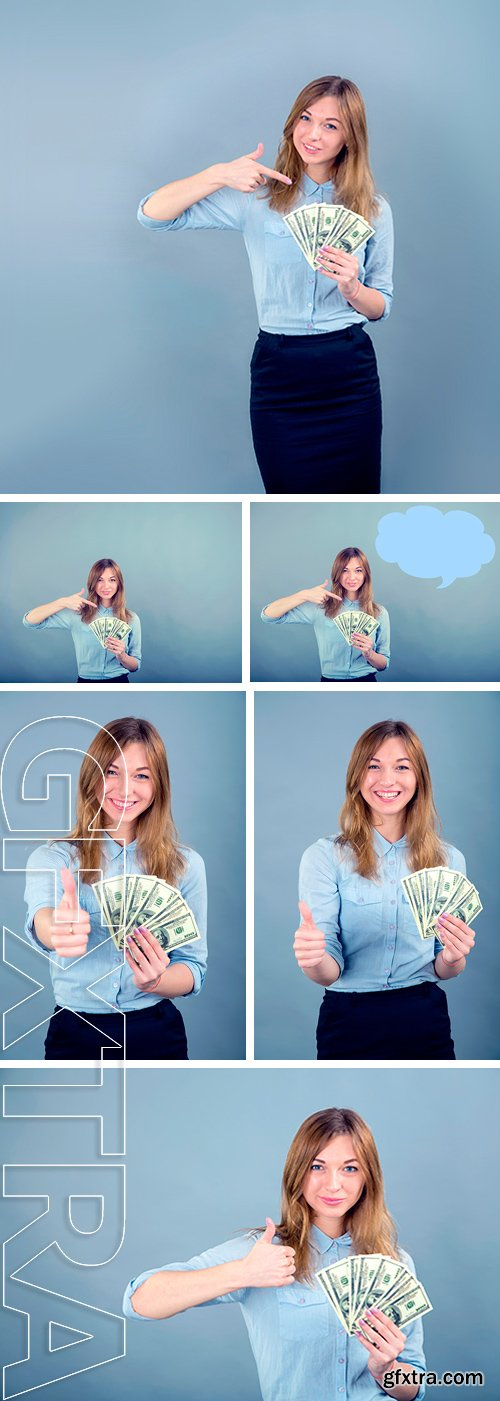Stock Photos - Happy young business woman with gesture. Beautiful smiling business woman standing against blue background. Woman holding a hundred dollar bills USA