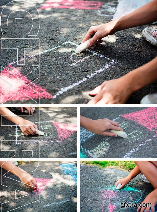 Stock Photos - Children draw in the park with chalks of various colors. Selective focus on hand