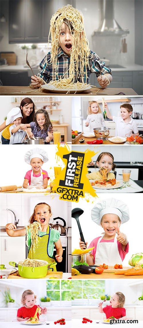Stock Photos Children eating spaghetti at kitchen