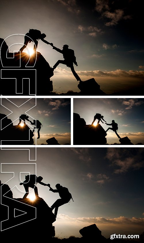 Stock Photos - Couple hiking help each other silhouette in mountains