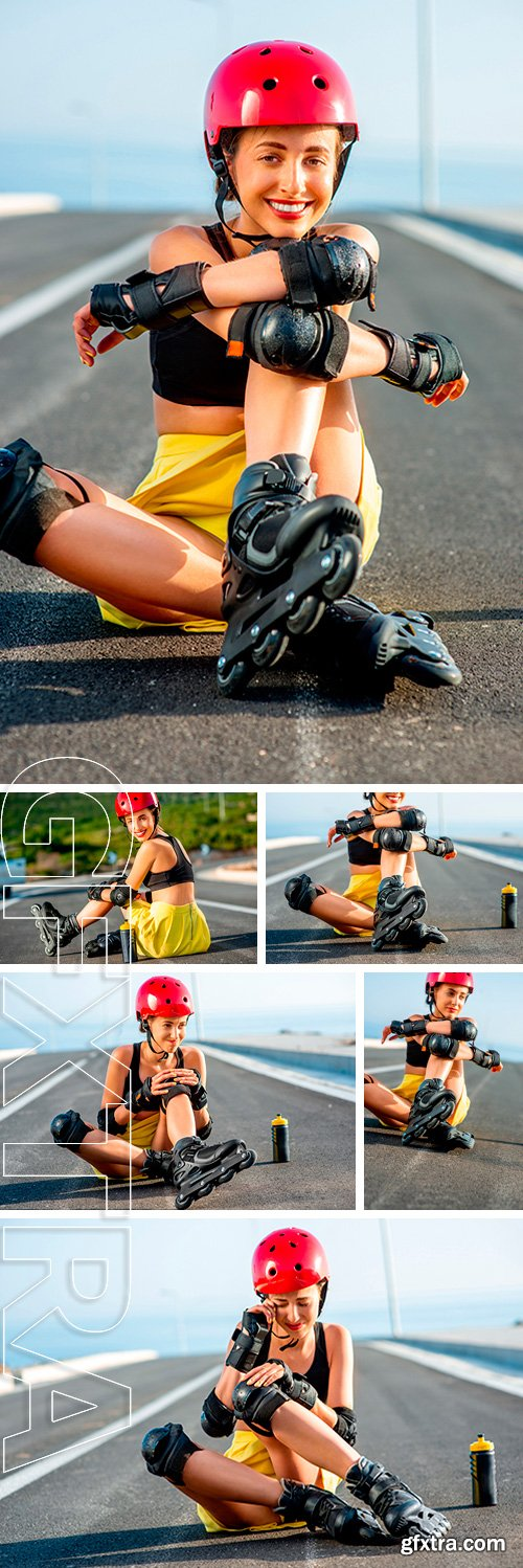 Stock Photos - Young sport woman with rollers in yellow skirt and red helmet with full protection wear sitting on the asphalt road