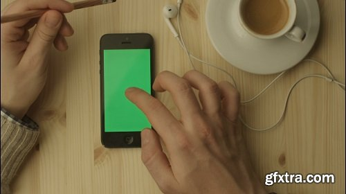 Phone with green screen laying on a wooden table