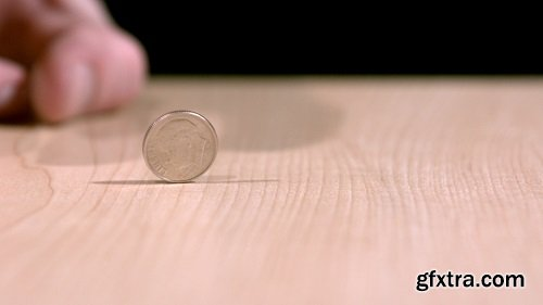 Slow motion flicking dime across table 2