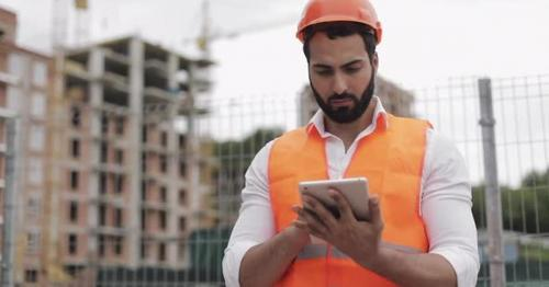 Architect Man Standing with Tablet on the Construction Site and Analyzing Scheme Project Plan - WCNTA37