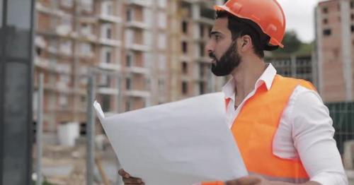 Architect Man Walking on the Construction Site and Analyzing Scheme Project Plan - PCW43H8