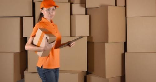 Beautiful Female Courier In Orange Uniform Delivering a Parcel Against Carton Stacks Backround - 4R9H2UP
