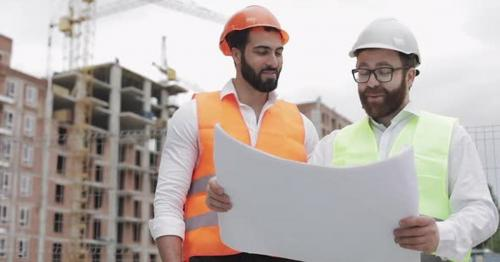 Smiling Male Construction Engineer Discussion with Architect at Construction Site or Building Site - ZL4SAQ6