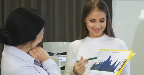 Young Businesswoman Showing Diagrams To Her Senior Colleague - WHKYRPM
