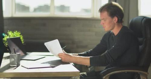 Young Thoughtful Businessman Sitting in the Office at the Table Near Notebook and Working - 7XSM2V9