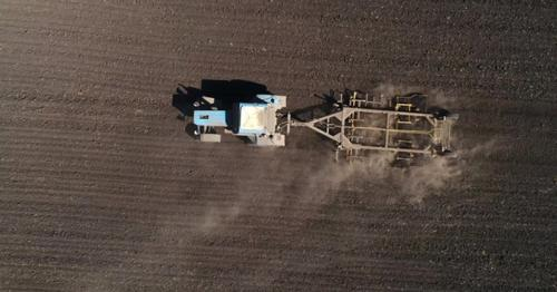 Aerial View of Agricultural Tractor Cultivating Field. Tractor At Work. - HXDBWQN