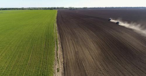 Aerial View of Agricultural Tractors Cultivating Field. - 6R9USEV