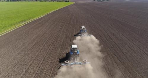 Aerial View of Agricultural Tractors Cultivating Field. - UC7XHYN