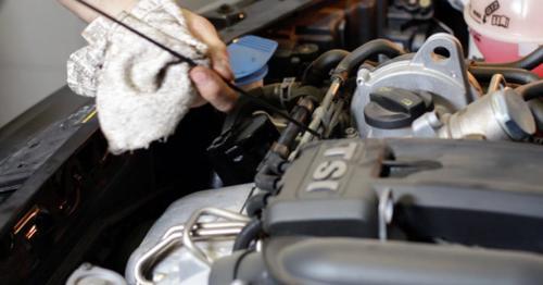 Car Repair Mechanic Checking the Oil Level - V2G6RLJ