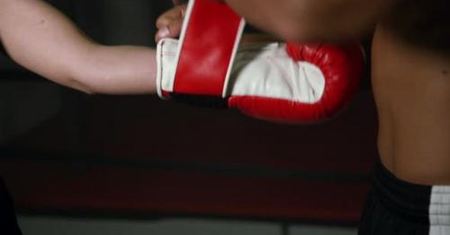 Coach Helps Women Boxer To Put On Gloves 17b - A5HLT7C
