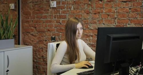 Female Specialist Looking at Computer Screen Sitting in Modern Office. - WUD5VT4