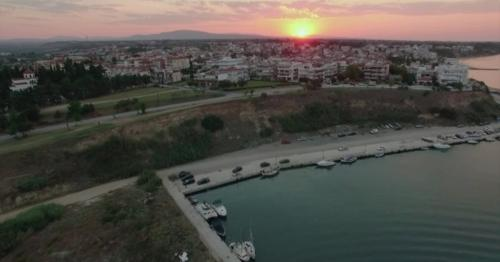 Flying Over the Quay and House Roofs at Sunset. Nea Kallikratia, Greece - V9MPH43