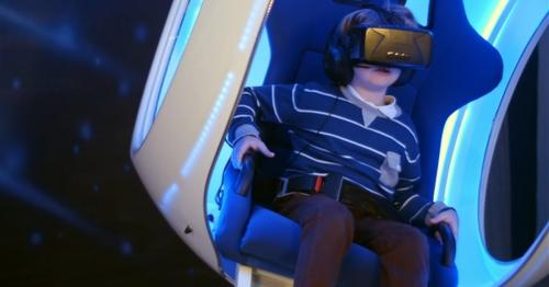 Little Boy Experiencing Virtual Reality Sitting in Interactive Moving Chair - YMSHKZ8