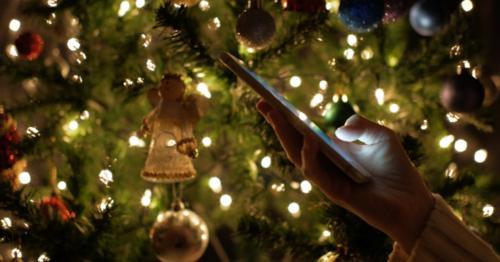 Using Smartphone At Christmas Tree Lights Background - EQXVACZ