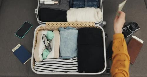 Woman's Hands Packing Suitcase for a Journey on the Bed at Home. Travel Preparations - BZU2QE6