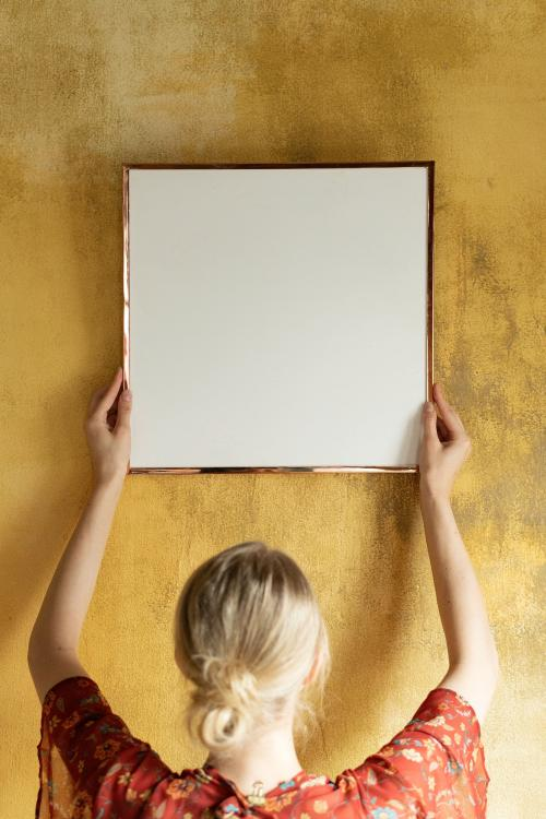 Woman hanging a frame mockup on a grunge yellow wall - 1212438