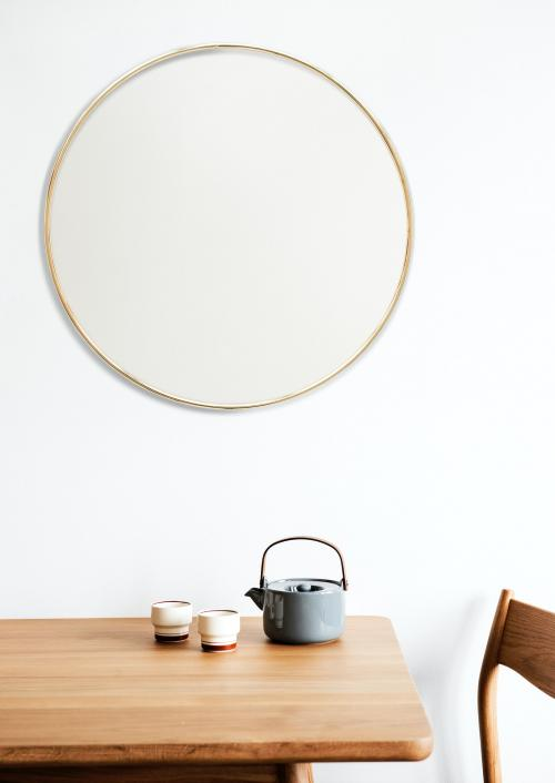 Golden frame on a white wall by a tea set - 1212841