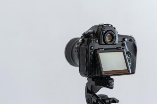 Digital camera on a tripod in a studio - 1225600