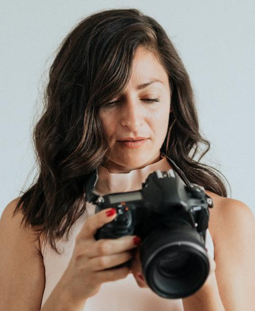 Female photographer holding digital camera - 1224219