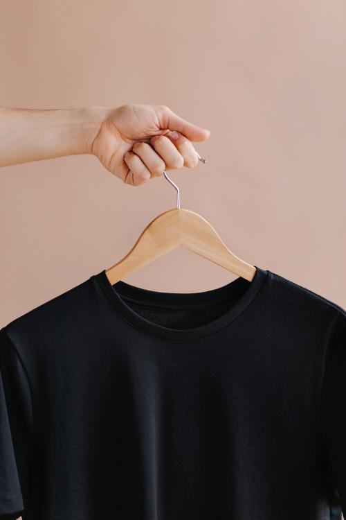 Hands holding a black t-shirt in a hanger - 1235371