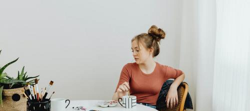 Female artist sitting thoughtfully while looking at her artwork - 592721