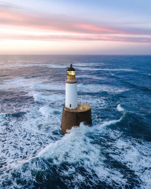 Waves hitting a lighthouse in Scotland - 1017138