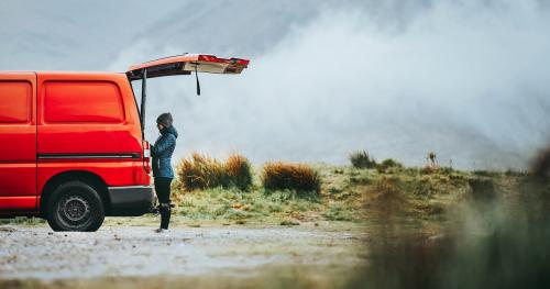 Woman standing by the red van in the highlands - 1077863