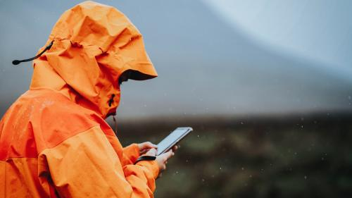 Woman using her mobile phone in the highlands - 1077891
