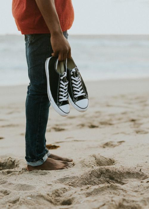 Black man carrying his shoes on the beach - 1079728