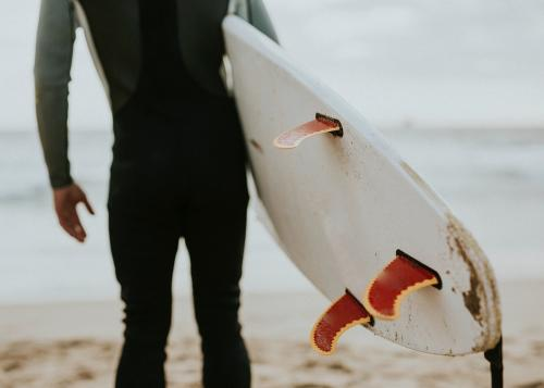 Man at the beach with his surfboard - 1079802