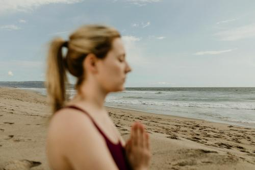 Woman practicing yoga on the beach - 1079811