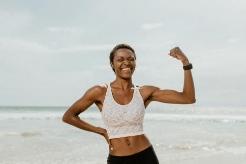 Cheerful black woman flexing her muscles by the seaside - 1079815