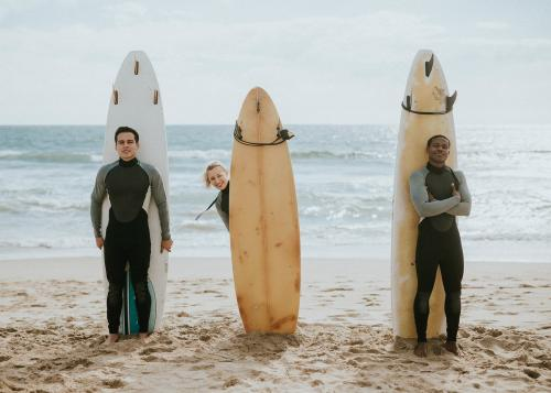 Happy friends surfing at the beach - 1079832