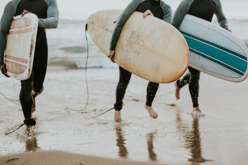 Happy friends surfing at the beach - 1079846