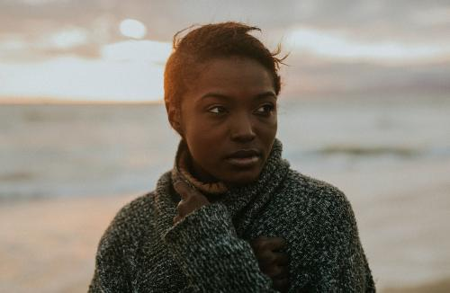 Black woman on the beach at sunset - 1079858