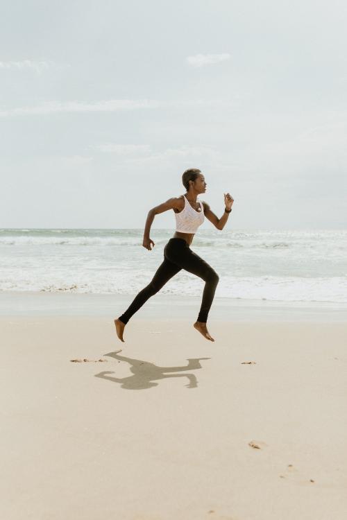Black woman running at the beach - 1079868