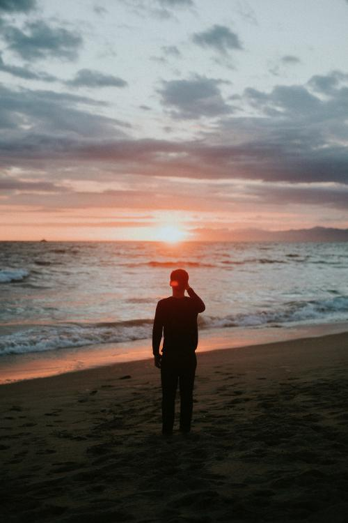 Man watching the sunset on the beach - 1079875