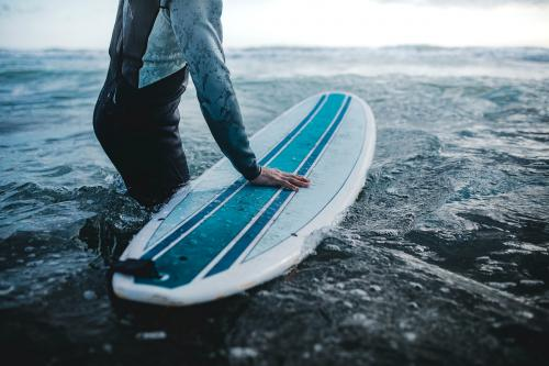 Man at the beach with his surfboard - 1079903