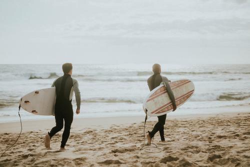 Surfers running on the beach - 1079934
