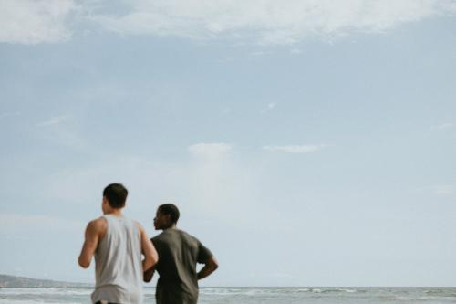 Friends jogging at the beach together - 1079936