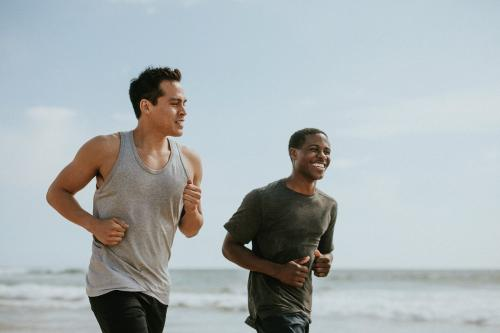 Happy friends jogging at the beach together - 1079969