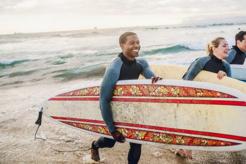 Cheerful friends surfing at the beach - 1079973